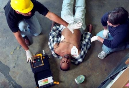 Image of construction worker using and AED.
