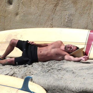 Image of surfer laying down next to surf board suffering from heat stroke